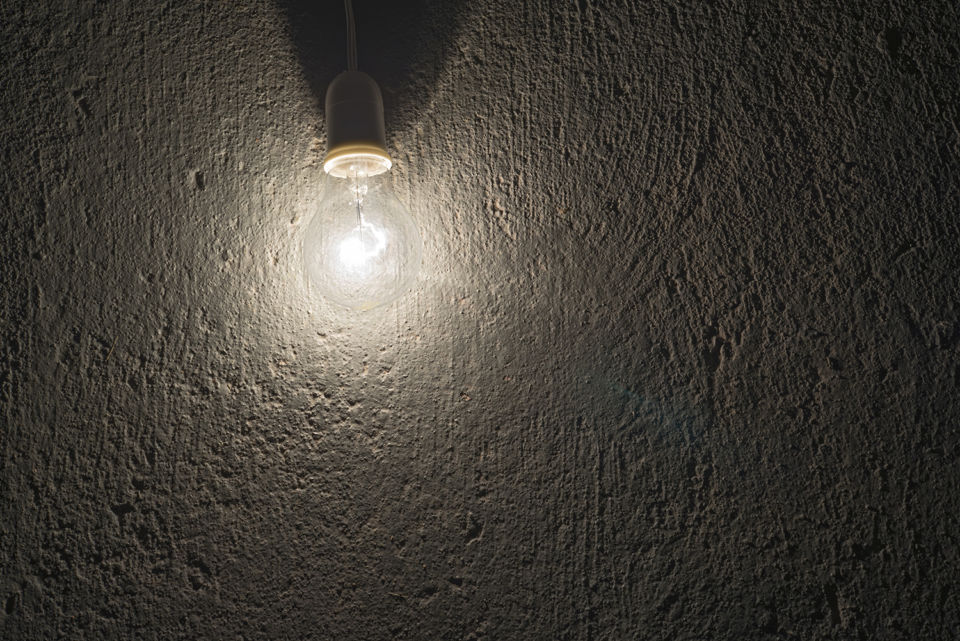 electric bulb on a rough concrete wall